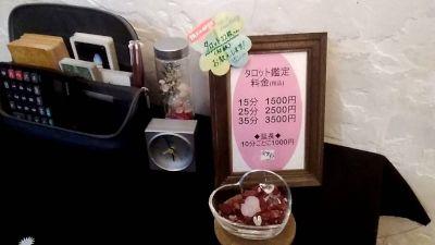 妃彩江先生が営む占い喫茶「安里彩」店内の占いテーブルと鑑定料のプレート